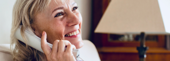 Senior woman smiling on corded phone
