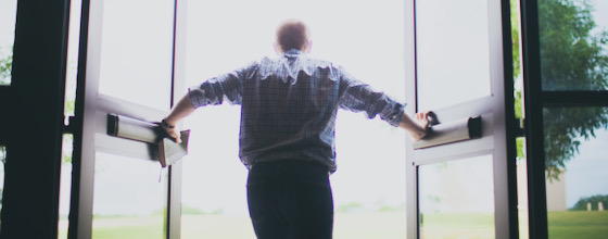 View from back of man opening doors outward and holding Bible