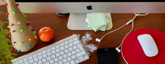 Desk with computer keyboard, mouse, earbuds, phone, notes, and Christmas decor