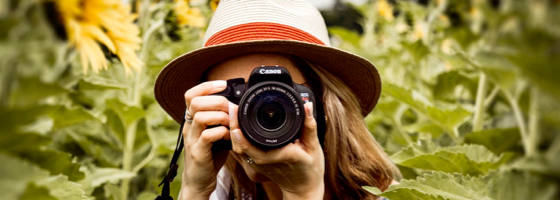 Woman with hat Holding Camera in Garden